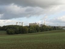 Une grande usine parmi la forêt et les champs verts image libre de droits