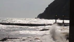 Une grande vague se casse au sujet d'un plan rapproché de brise-lames sur un fond de coucher du soleil projectile Paysage marin V image libre de droits