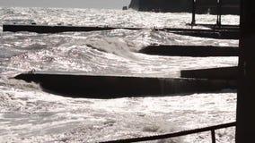 Une grande vague se casse au sujet d'un plan rapproché de brise-lames sur un fond de coucher du soleil projectile Paysage marin V images libres de droits