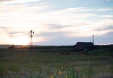 Une grange et un Wildmill rustiques au coucher du soleil photos stock