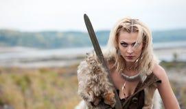 Une guerrière de femme dans le style scandinave de Vikings s'est habillée dans un loup que la peau du ` s se tient avec une épée  images stock
