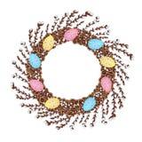 Une guirlande de jeunes branches de saule, décorée des oeufs de pâques colorés photos stock