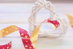 Une guirlande de rotin dans une forme de coeur avec un ruban Image libre de droits