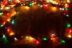 Une guirlande rougeoyante de Noël à l'arrière-plan de la toile de jute dans l'obscurité Photographie stock