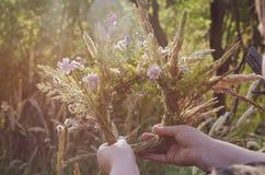 Une guirlande traditionnelle des herbes et des fleurs de champ dans les mains de la fille au soleil Préparation au rite de la cél photographie stock