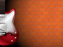 Une guitare devant un mur de briques Photos libres de droits