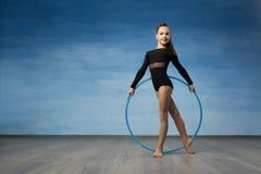 Une gymnaste de fille dans un maillot de bain noir regarde dans le profil dans les mains d'un cercle gymnastique images stock
