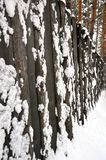 Une haute barrière en bois couverte de neige Images stock