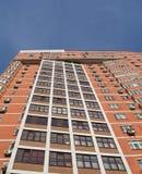 Une haute construction urbaine, brique rouge-brun, ciel bleu Images libres de droits