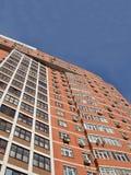 Une haute construction urbaine, brique rouge-brun, ciel bleu Photos stock