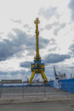 Une haute grue de port dans bleu et jaune dans la perspective d'un ciel dramatique Images libres de droits