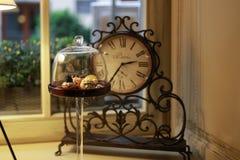 Une horloge de cru sur un rebord de fenêtre derrière photos stock