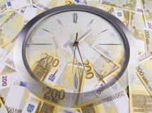 Une horloge et 200 euro billets de banque Images libres de droits