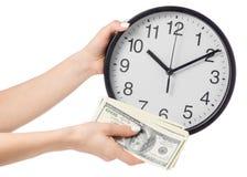 Une horloge sur des dollars d'une main femelle et d'argent Photographie stock libre de droits