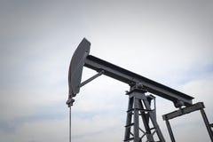 Une huile de pompes de pompe à huile au milieu d'un champ images stock