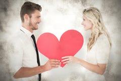 Une image composée de jeunes couples attrayants tenant le coeur rouge Image stock