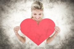 Une image composée de la jeune blonde attirante montrant le coeur rouge Photo libre de droits