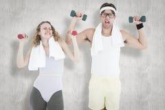 Une image composée des haltères de levage de couples geeky de hippie dans les vêtements de sport Photographie stock libre de droits