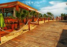 Une image d'un restaurant ou d'une barre de plage qui se tient sur le sable près des palmiers Photographie stock libre de droits