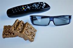 Une image de concept de televison de observation avec les verres 3D et le maïs éclaté, casse-croûte Photographie stock libre de droits