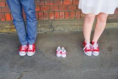 Une image des adultes dans des espadrilles rouges à côté des paires de bébé d'espadrilles Concept de grossesse et d'attente Photographie stock libre de droits