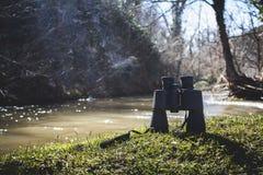 Une image des jumelles sur l'herbe par la rivière avec des sunlights photo stock