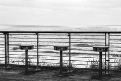 Une image monochrome de trois chaises sur le bord de la mer Photo libre de droits