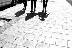 Une image noire et blanche de trois personnes et de leurs ombres au sol Photos libres de droits