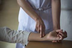 Une infirmière comptant la fréquence du pouls patiente du ` s image stock