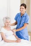 Une infirmière de sourire avec son patient Photo libre de droits
