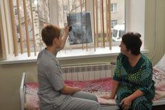 Une infirmière et un patient plus âgé observent un rayon X dans l'hôpital images libres de droits