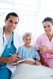 Une infirmière prenant la température de son patient Photographie stock libre de droits