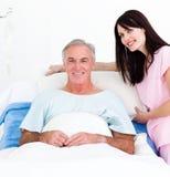 Une infirmière réglant des oreillers à un patient aîné Images libres de droits