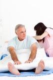 Une infirmière réglant des oreillers à un patient aîné Photo stock