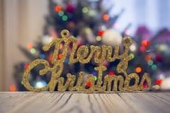 Une inscription brillante de Joyeux Noël sur une table en bois contre l'arbre de Noël décoré Image libre de droits
