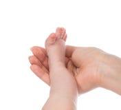 Une jambe de pied de bébé d'enfant nouveau-né de mois dans la main de mère Photographie stock libre de droits