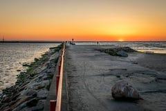 Une jetée ou une jetée avec les personnes silhouettées avec un coucher du soleil en mer photos stock