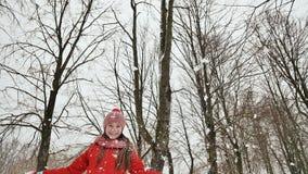 Une jeune écolière joyeux jette une boule de neige et la casse avec une paume quand elle tombe Émotions de joie Amusement d'hiver banque de vidéos