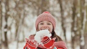 Une jeune écolière joyeux jette une boule de neige et la casse avec une paume quand elle tombe Émotions de joie Amusement d'hiver clips vidéos