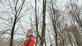 Une jeune écolière joyeux jette une boule de neige et la casse avec une paume quand elle tombe Émotions de joie Amusement d'hiver photographie stock libre de droits