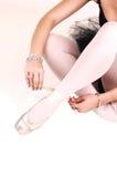 Une jeune ballerine attachant ses chaussons de ballet. Images stock
