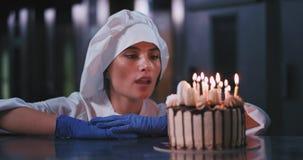 Une jeune belle dame portant des gants bleus et un uniforme de cuiseurs souffle les bougies sur le gâteau banque de vidéos