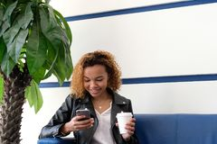 Une jeune belle femme d'Afro-américain dans une veste en cuir avec un verre de livre blanc se reposant sur un sofa bleu près d'un photos stock