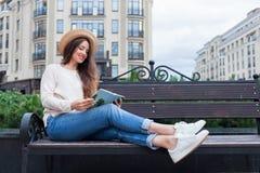 Une jeune belle femme dans un chapeau élégant s'assied sur un banc dans un nouveau voisinage résidentiel et lit un livre de papie Image stock