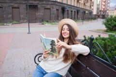 Une jeune belle femme dans un chapeau élégant s'assied sur un banc dans un nouveau voisinage résidentiel et lit un livre de papie Images libres de droits