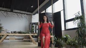Une jeune belle femme enceinte dans une robe rouge et longue swading l'amusement à l'oscillation dans une grande salle élégante d banque de vidéos
