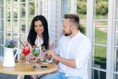 Une jeune belle femme est venue une date chez un type brutal élégant La fille sourit dans l'embarras et prend son propre dessert photos libres de droits