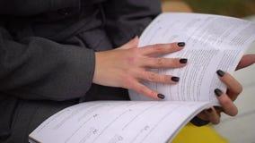 Une jeune belle femme lisant le journal en parc par automne Plan rapproché des mains et des pages du magazine banque de vidéos