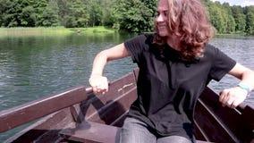 Une jeune belle femme navigue sur un bateau sur le lac banque de vidéos