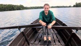 Une jeune belle femme navigue sur un bateau sur le lac clips vidéos